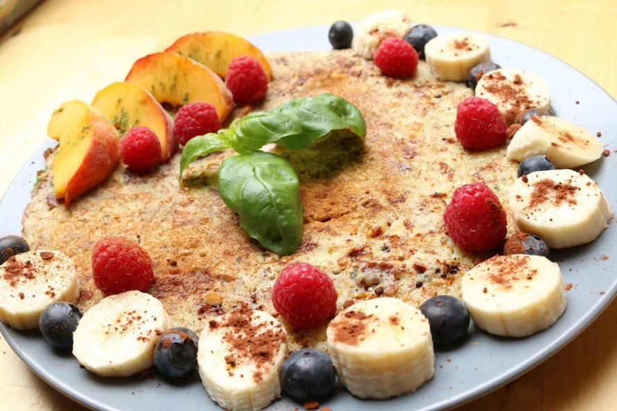 stack of pancakes covered in berries and bananas