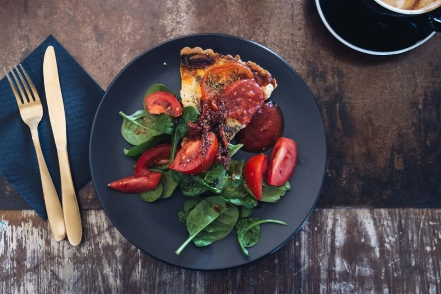 quiche with tomatoes on a black plate