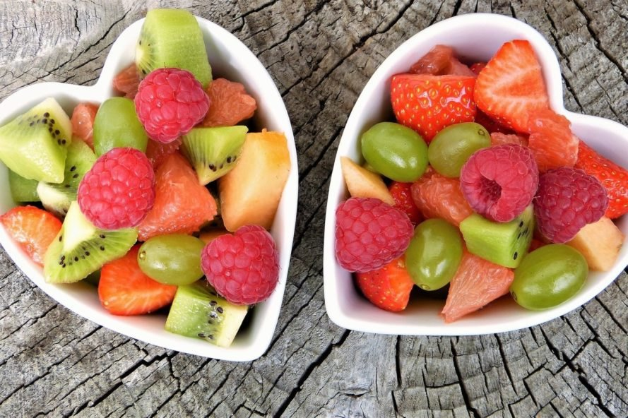 white heart-shaped bowls filled with fruit