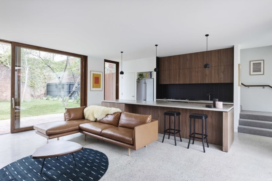 kitchen and living area of the home with brown furniture and wood cabinets