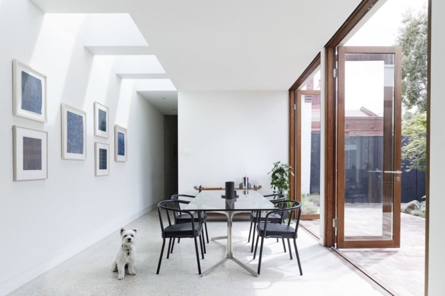 dining area with white walls and black table and chairs