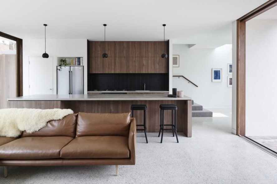 brown couch is positioned in front of kitchen area
