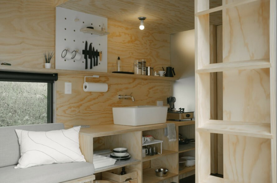 long wooden sofa and kitchen area inside tiny cabin
