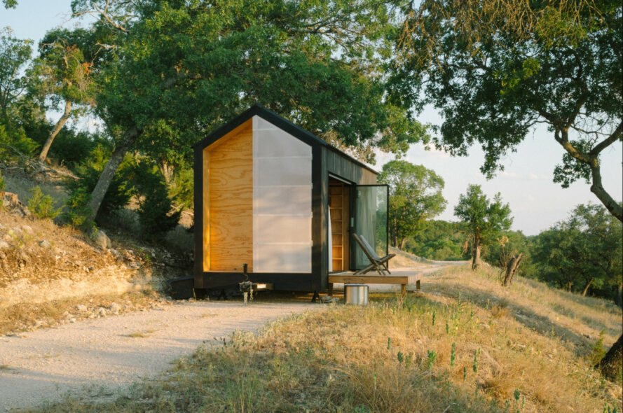 black tiny cabin on gravel path