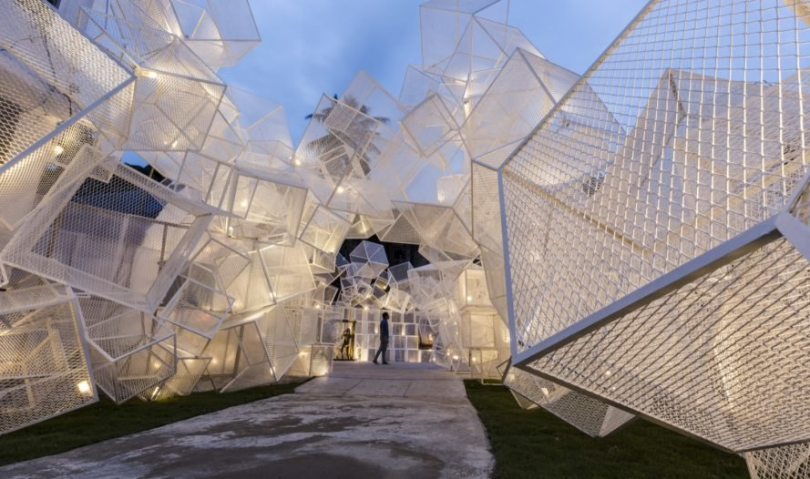entrance to pavilion made of white mesh cubes