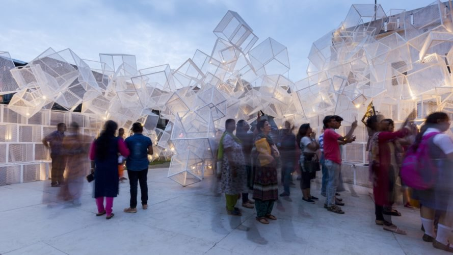people looking at white mesh cube sculptures
