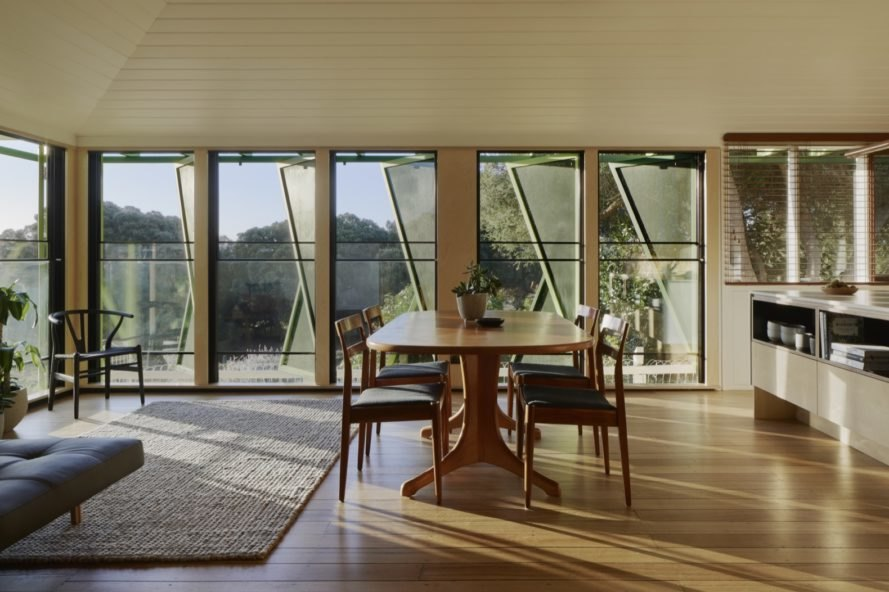 wood floors line the dining and living area of the home with a wood table and outside views from the shutter