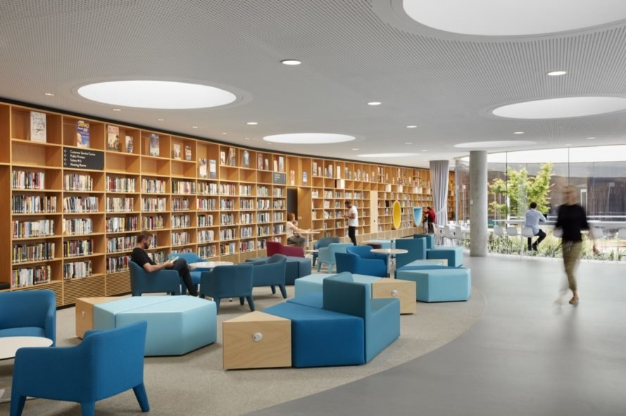 library with wall of books and blue seating