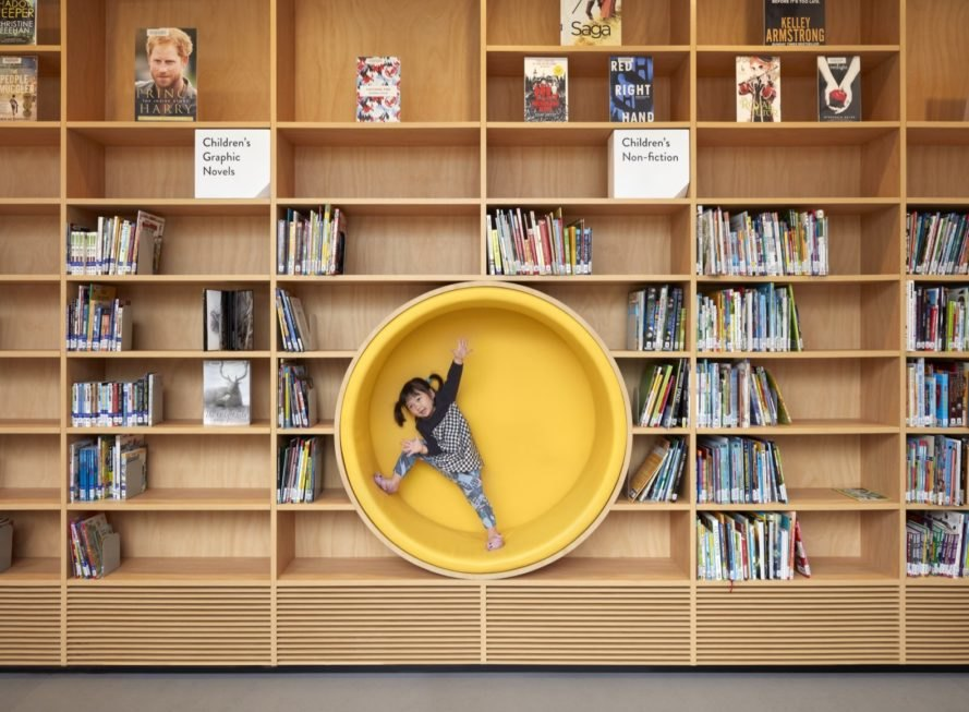 child climbing in yellow circular cutout in the middle of bookshelves