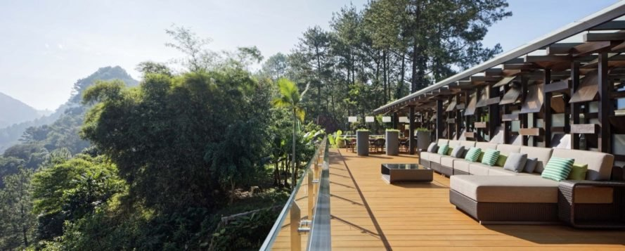 wooden outdoor deck surrounded by greenery