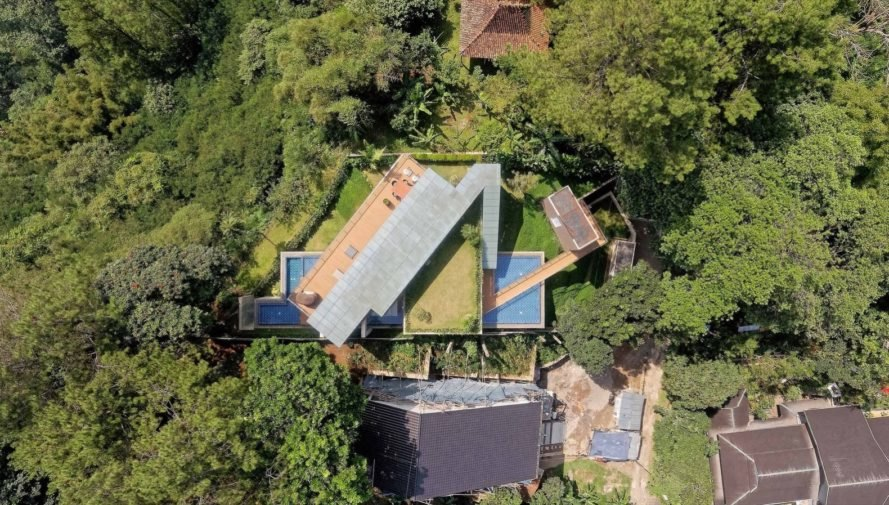 aerial view of green-roofed home with pool