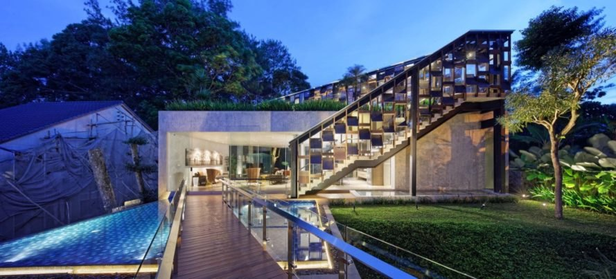 home with wooden deck and green roof lit up at night