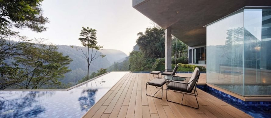 lounge chairs on wood deck facing pool and jungle