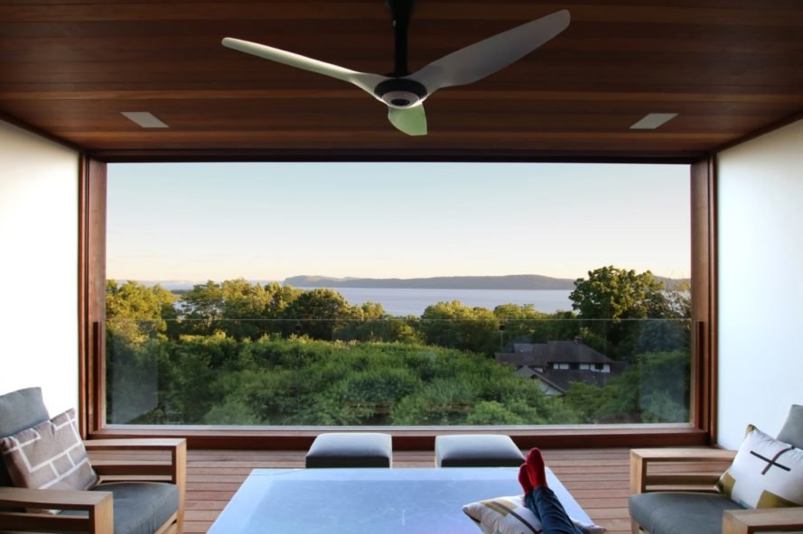 covered outdoor patio with gray seats and views of Hudson River