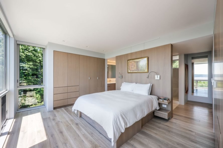 bedroom with white bed and light wood walls