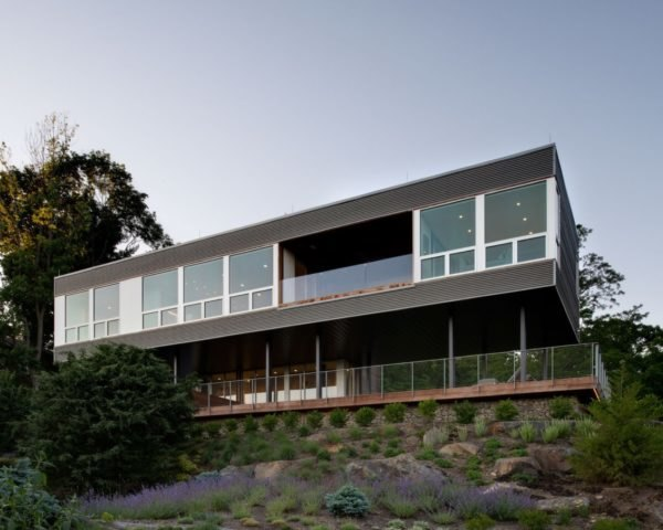 elevated gray home with large windows