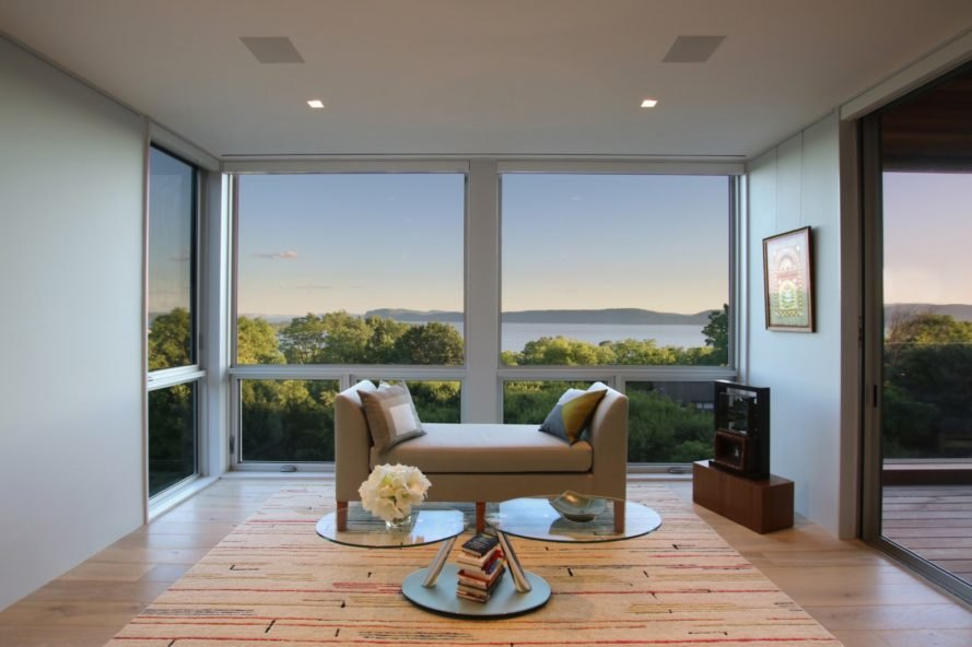 small tan seat in front of glass walls with views of Hudson River