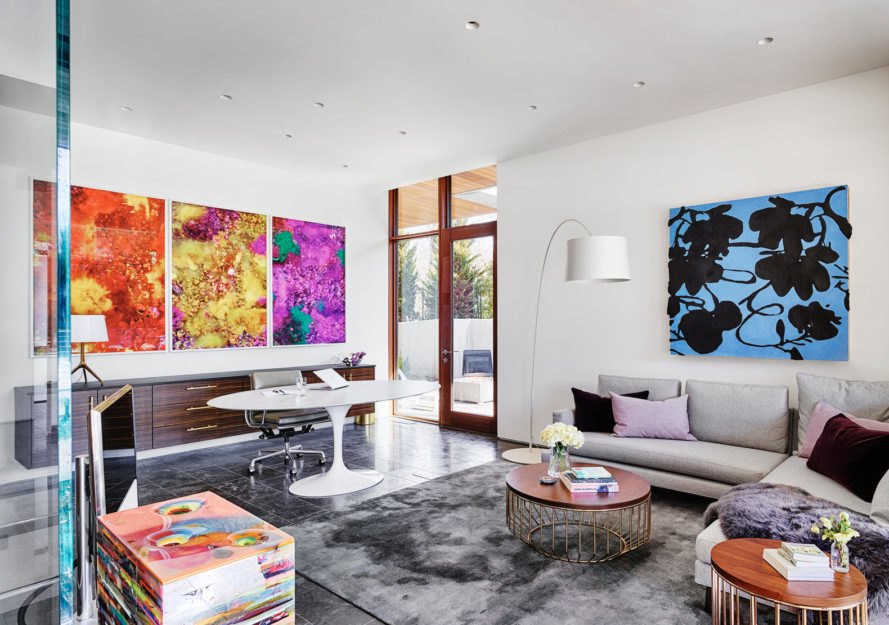 colorful art surrounds light colored furnishings with dark gray colored floor and rug