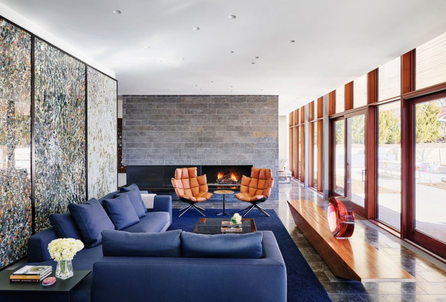 living area of the home with blue couches and fireplace with large windows