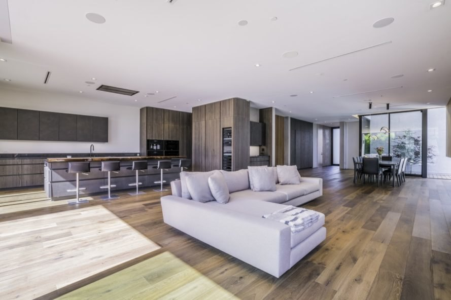 wood floors throughout the home's base floor with big windows letting in light towards the kitchen and living room