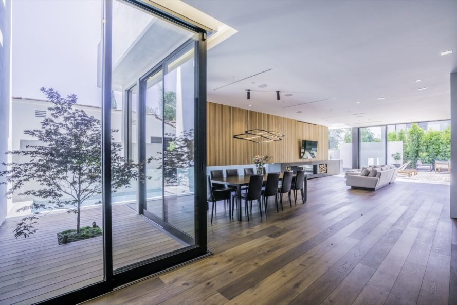 floor to ceiling windows are placed on opposite ends of the home letting in light to dining and living room