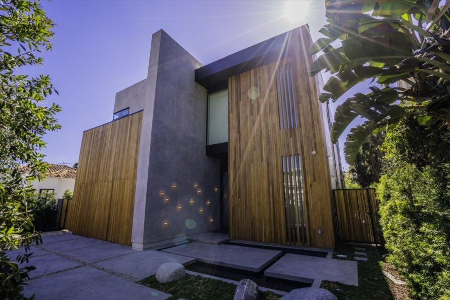 exterior view of the home's entrance with wood finishing and modern cement design on entrance floor