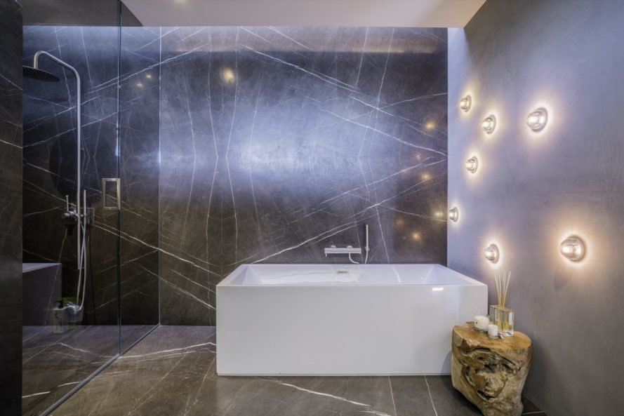 modern white tub in the bathroom with shower space beside it