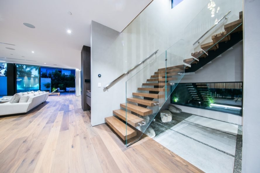 stair case with wood steps and glass rails