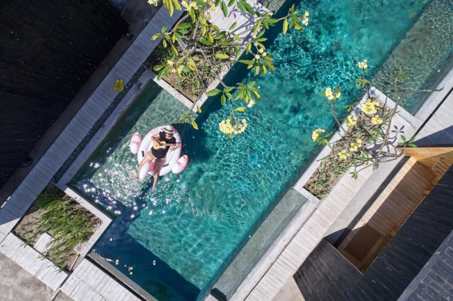 aerial shot of woman on a float in a pool