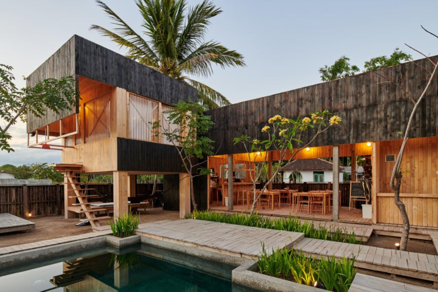 charred timber huts in front of a pool