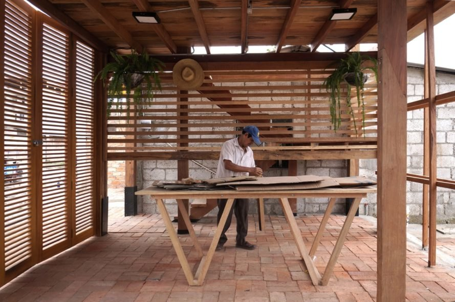 person working on a wood table inside a wood building