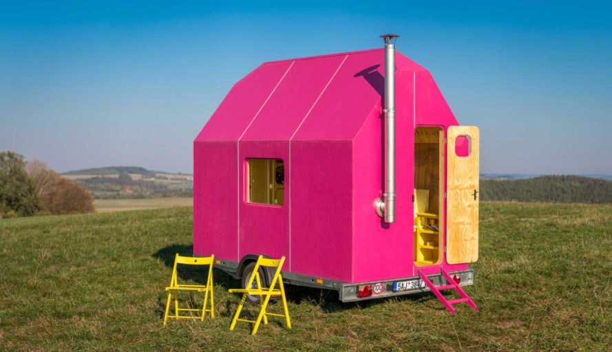 A tiny pink home with two yellow chairs.