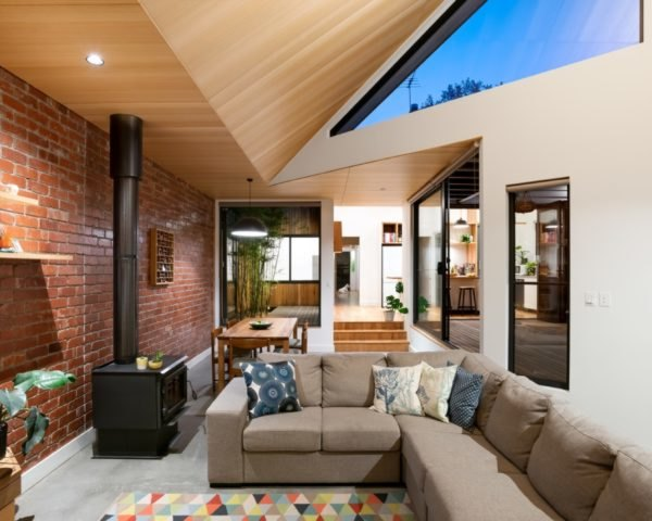 living room with exposed brick wall and tan sectional sofa