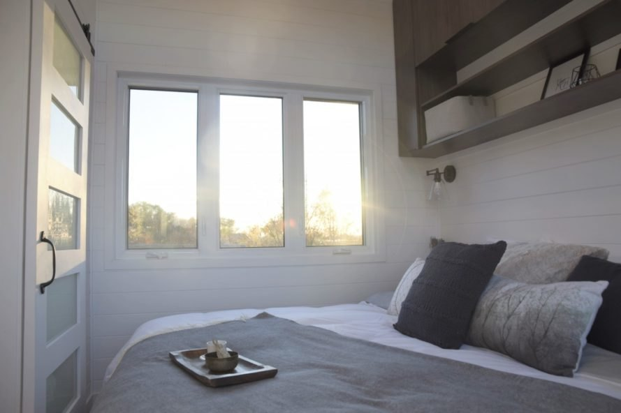 bed with white and grey pillows and blankets and three windows