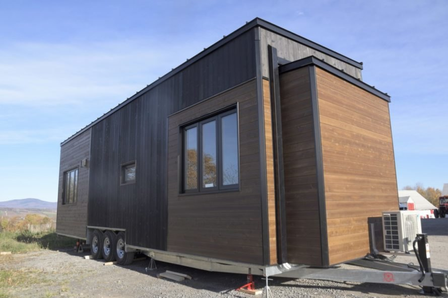 a wooden tiny home on wheels with windows