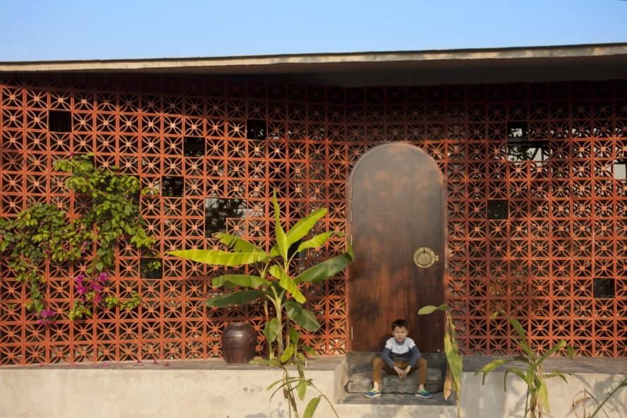 child sits on home's entry doorway near banana trees