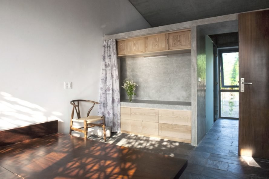 concrete walls inside bedroom with large windows