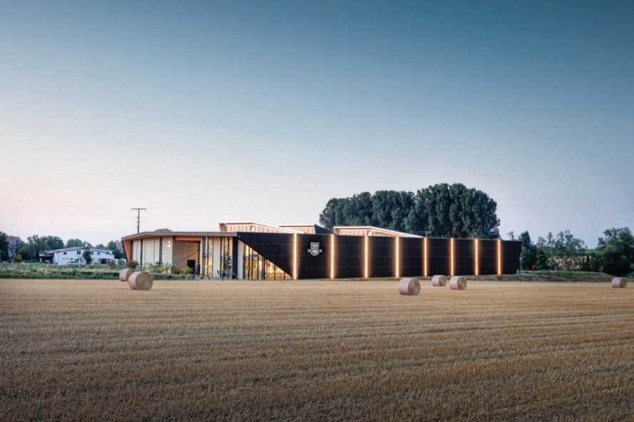 dark timber building with facade lighting and a farm in the foreground
