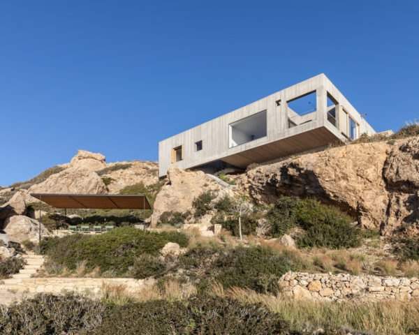 square concrete home on a rocky cliffside