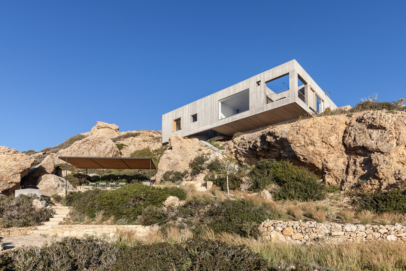 Concrete home perched on Greek island cliffside designed with large cut outs to frame the amazing sea views
