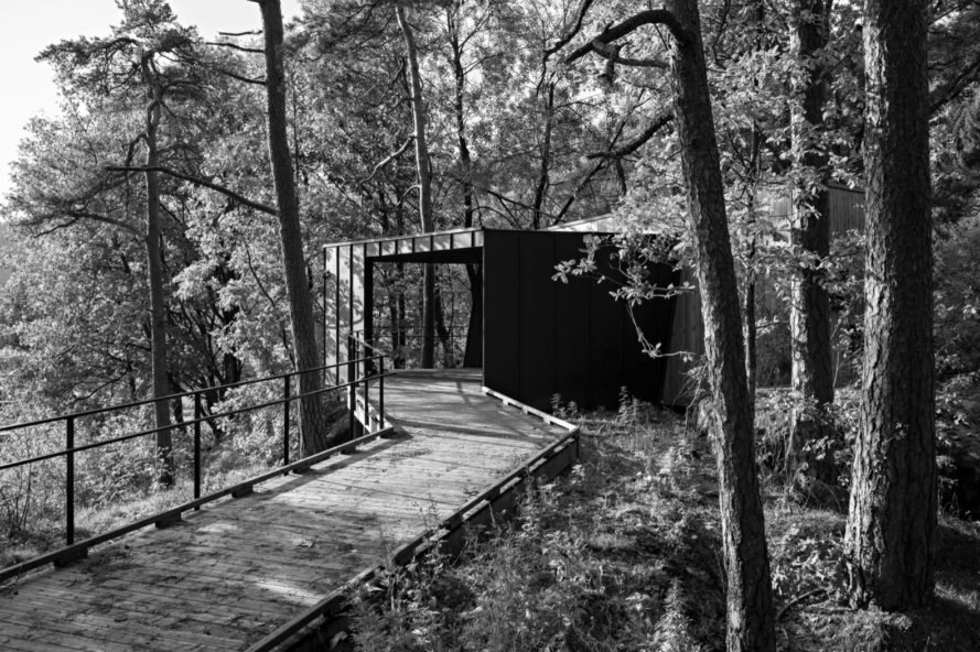 black and white image of wooden walkway leading to wood cabin in a forest