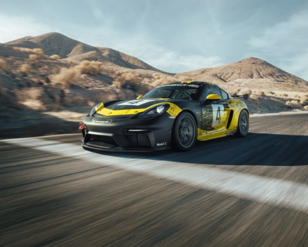 exterior of black and yellow porsche cayman on race track
