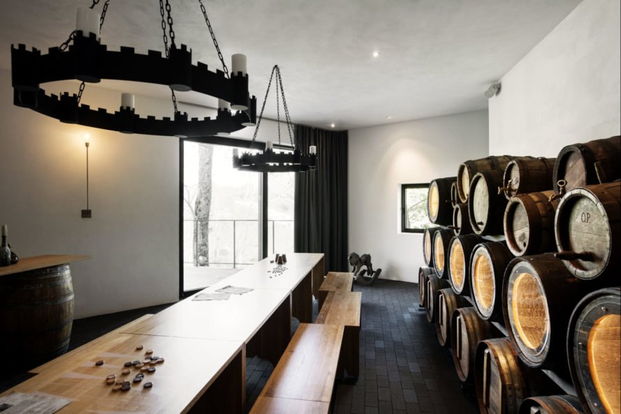 long wooden table with barrels on the side wall