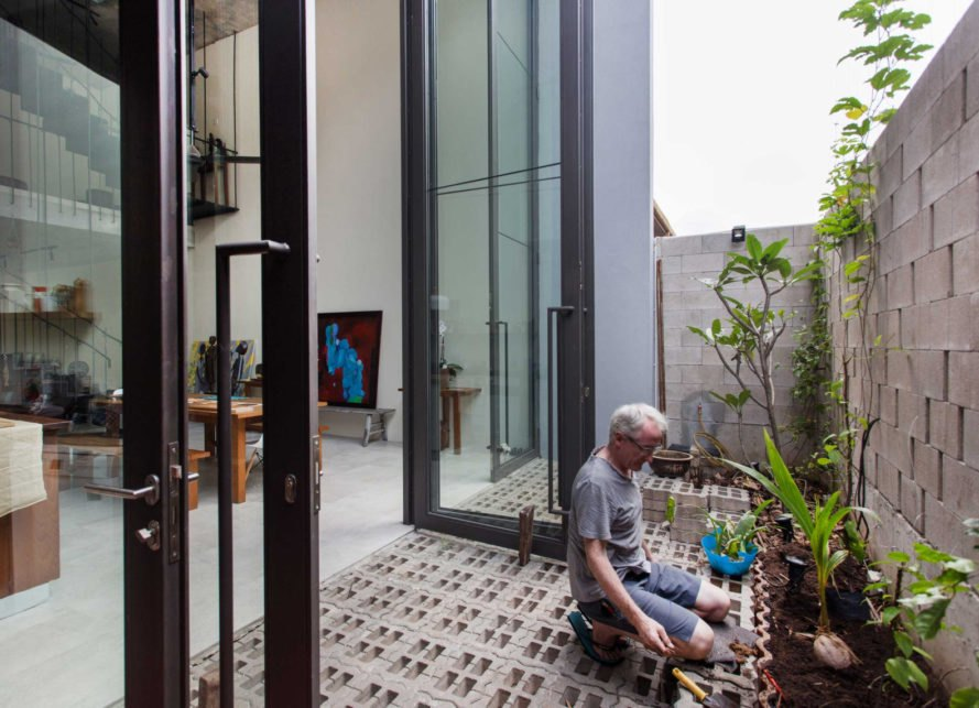 man planting in pots on open-air porch with glass doors