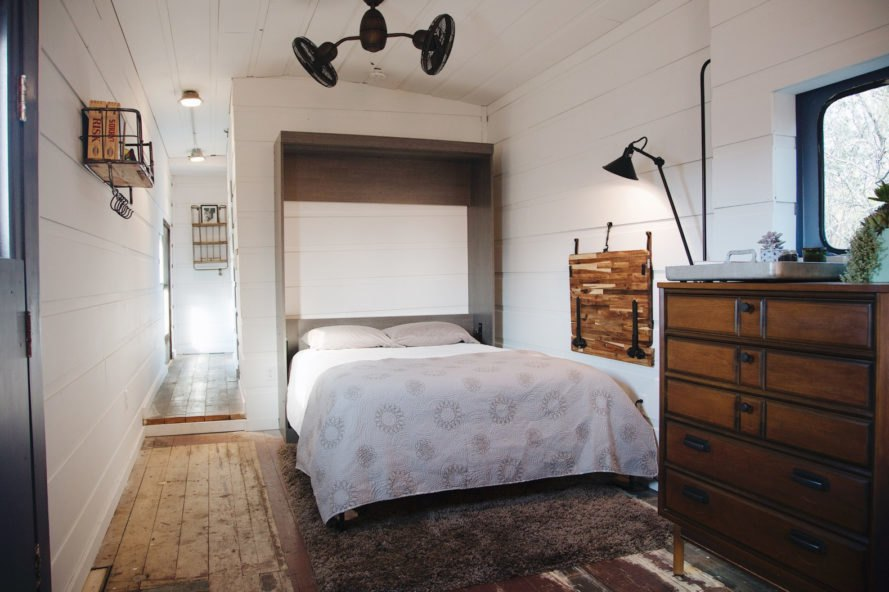 bedroom with all white walls and wooden furnishings
