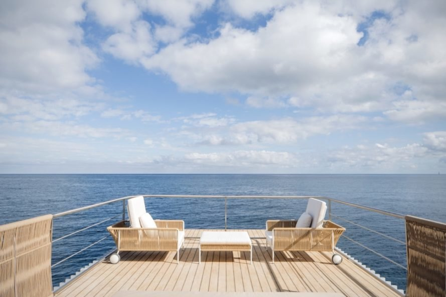 upper wood deck with white and wicker chairs