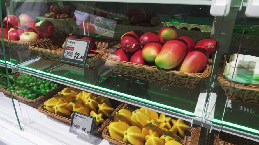 fake fruits on display behind glass counter