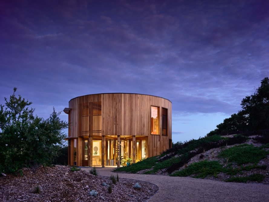 round timber beach house lit from within at dusk