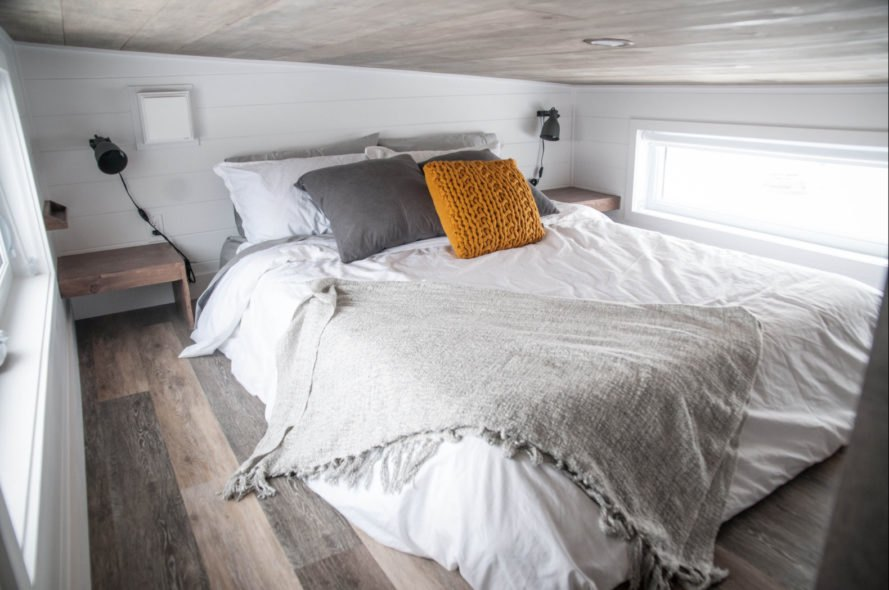 queen sized bed with orange and grey pillows