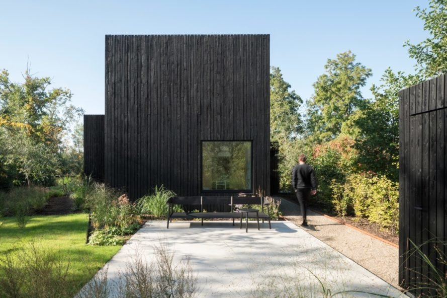 all black home with walkway surrounded by greenery